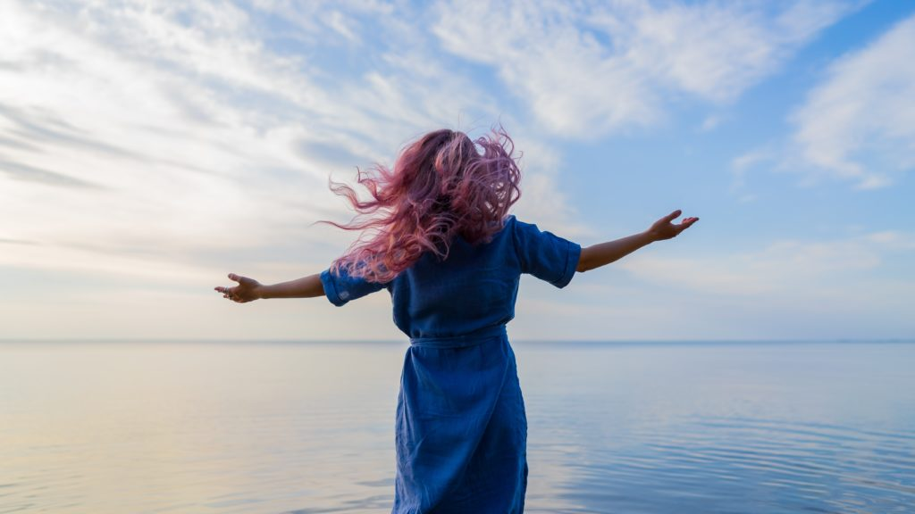 This woman standing on a beach with her arms outstretched is demonstrating how filling up on nature can develop mental resilience and reduce stress.
